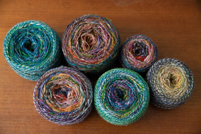 Six cakes of two-ply handspun yarn in rainbow colours arranged on a table.