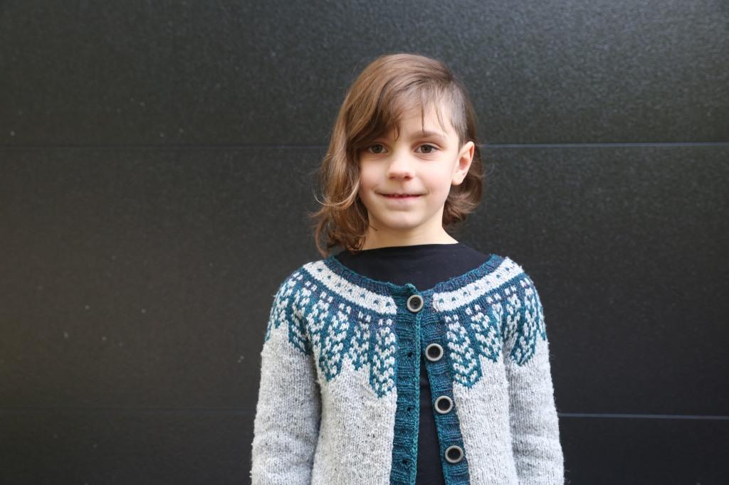 A child in a grey cardigan with a blue colourwork yoke.