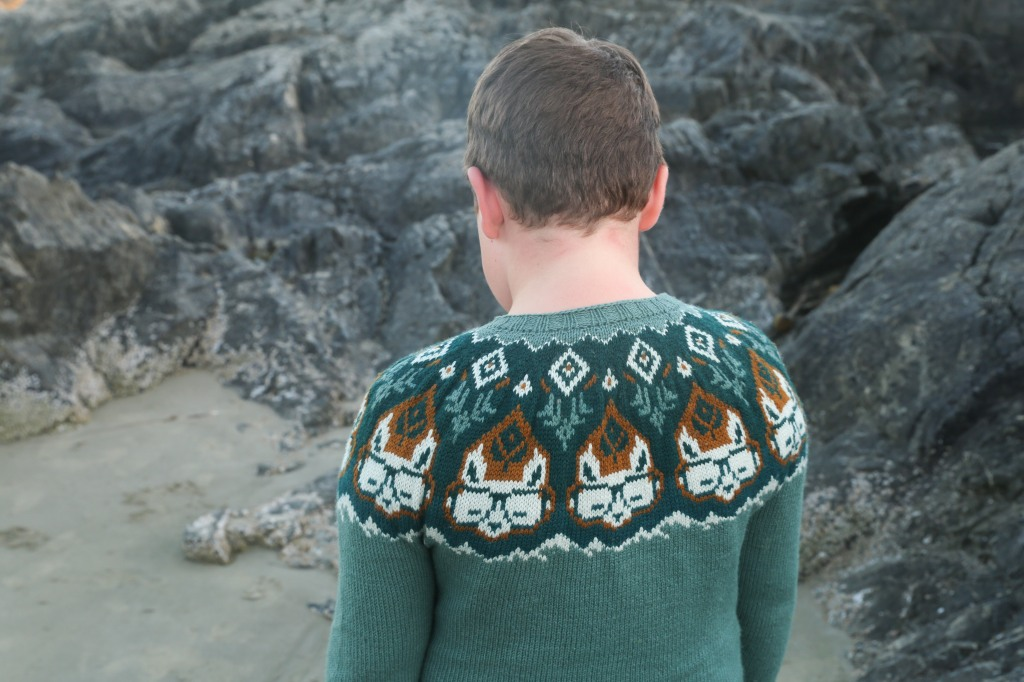 A child in a light teal sweater with a colourwork yoke.