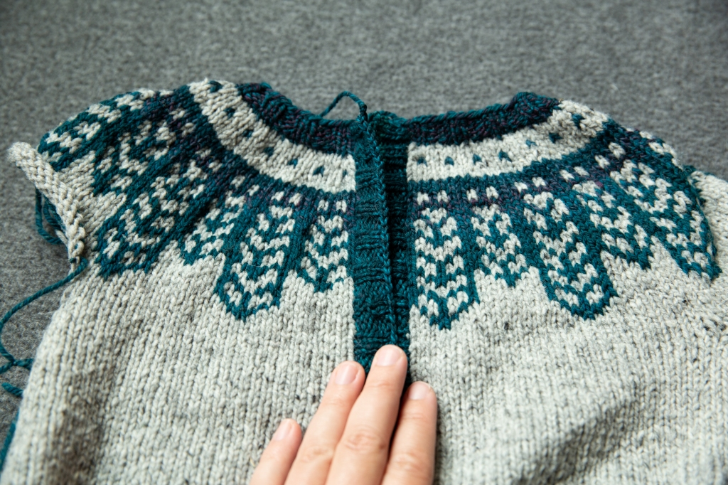 A grey cardigan with a blue colourwork yoke. The colourwork pattern is misaligned at the centre.