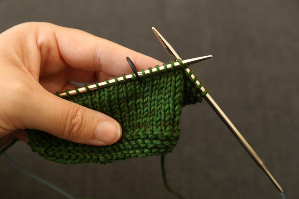A bit of green knitting on the needles with a black circular stitch marker 6 sts from the end of the needle.
