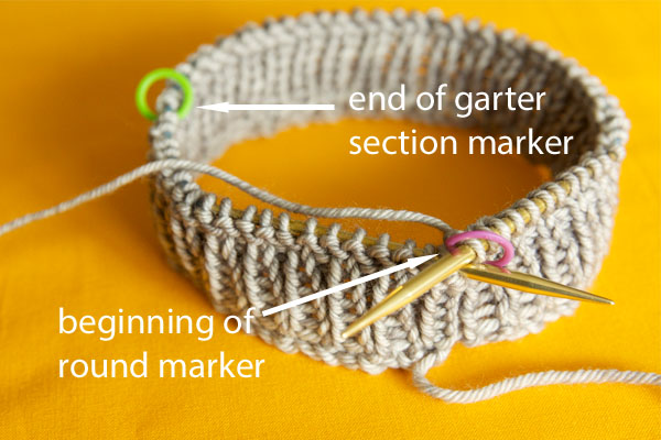 The ribbing of a knit hat on the needles with 2 markers in the work. Arrows point to each marker, one with the words 'beginning of round marker' and the other with 'end of garter section marker'