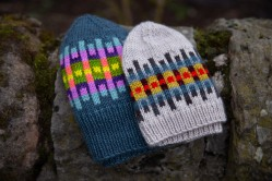 Two colourwork hats on a wall