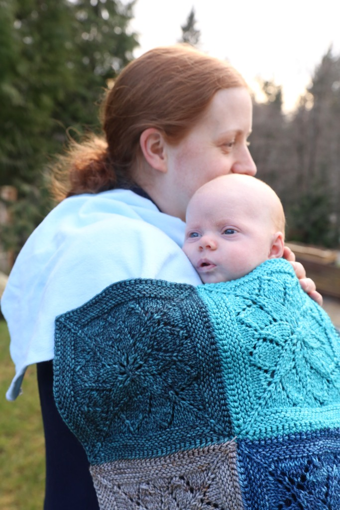 A woman holding a babe draped in a blue lace blanket.