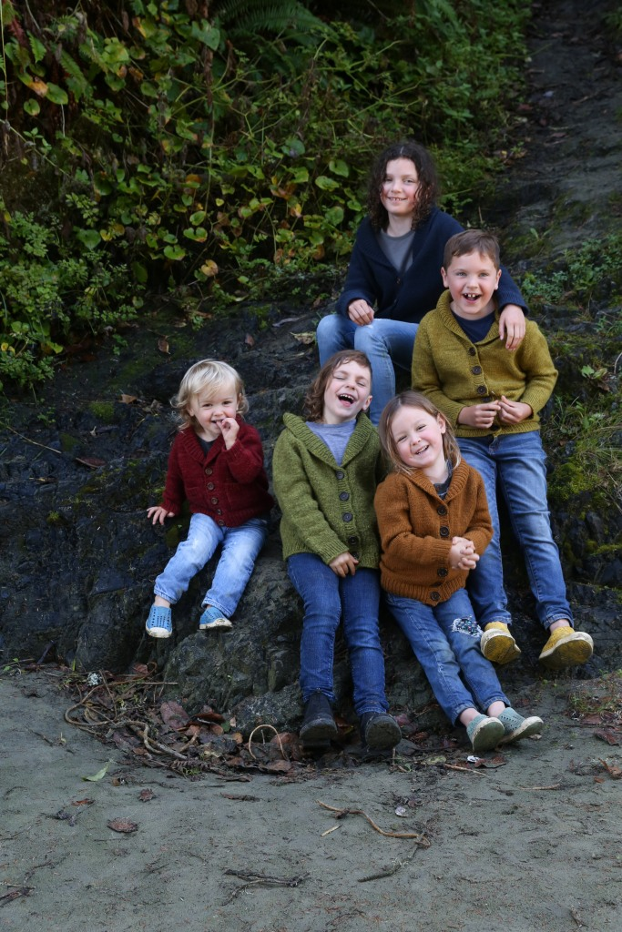 Five children in a rainbow of handknit sweaters.