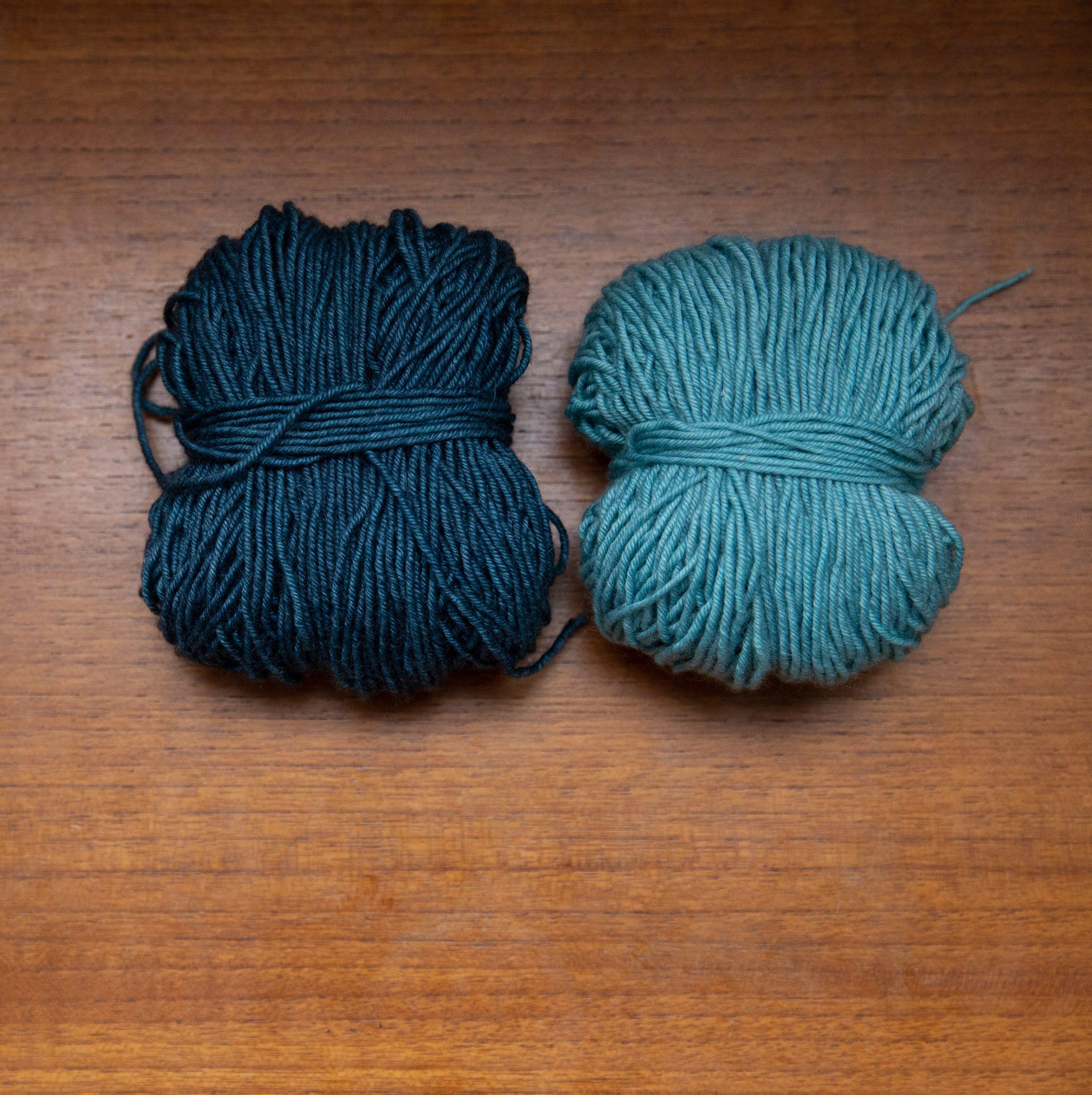 A ball of dark grey-blue yarn and a ball of light grey-blue yarn