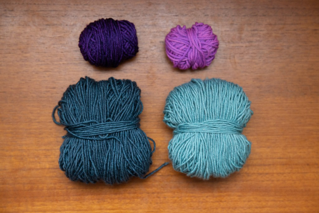 A ball of dark grey-blue yarn and a ball of light grey-blue yarn, with balls of dark purple and light purple above.