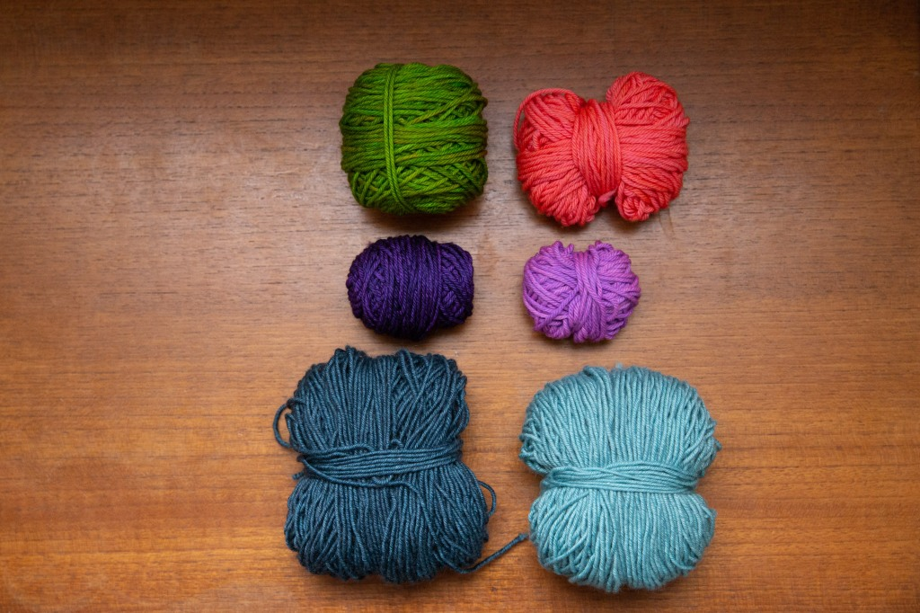 Two columns of yarns; on the left are dark blue, dark purple, and vivid green, on the right are light blue, light purple, and vivid neon pink