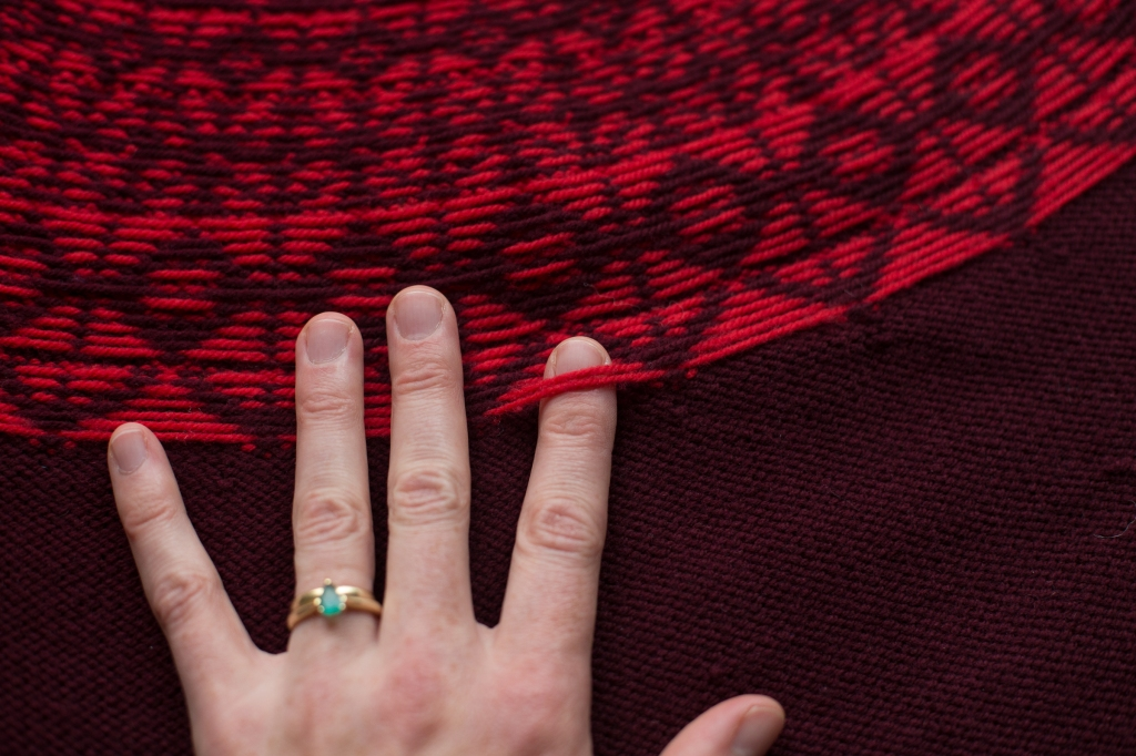 The inside of a colourwork yoke with a hand showing the float
