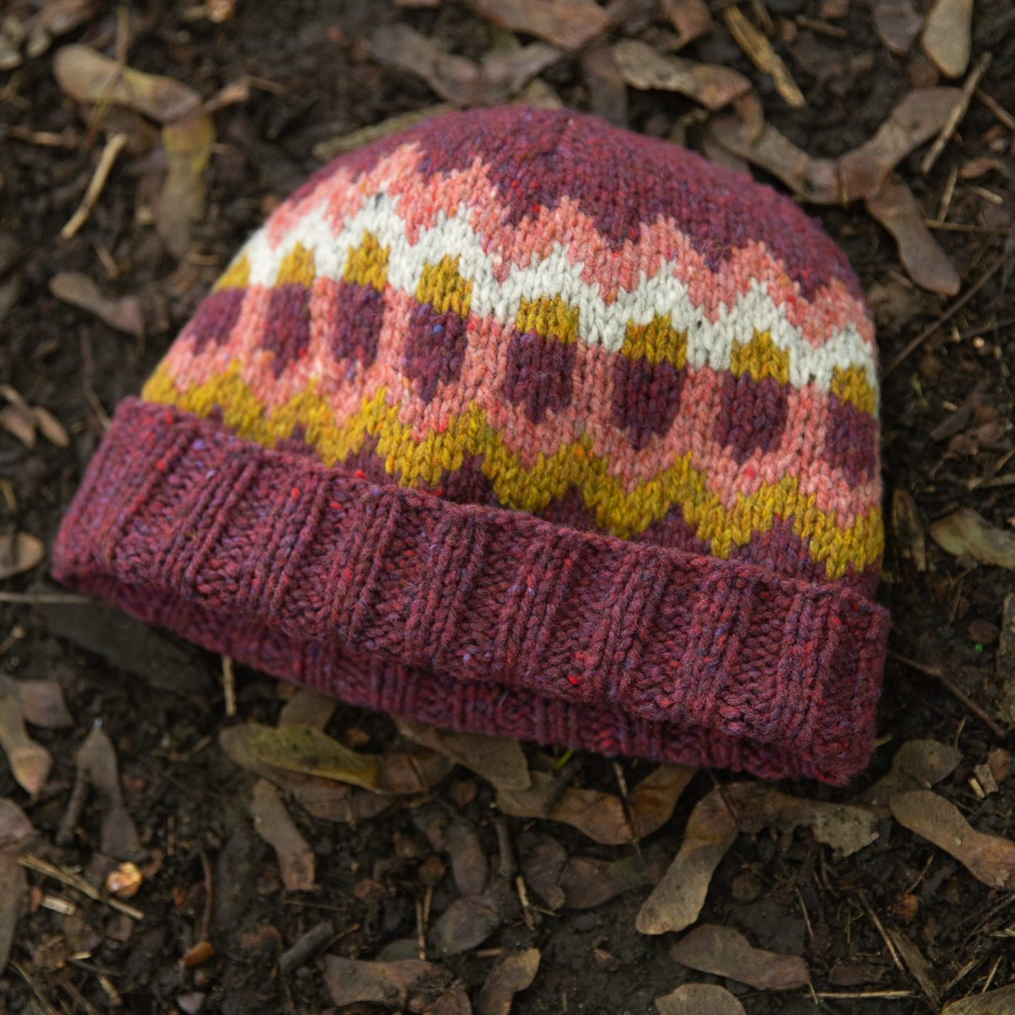 A colourwork hat on ground. The hat is a purple-ish pink with mustard, pink, and white colourwork motifs.