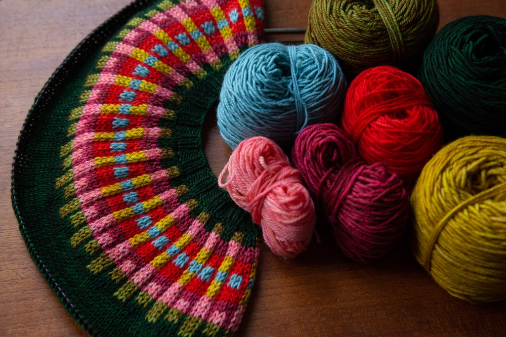 A sweater yoke in progress with all of the yarns used beside it